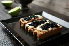 Sandwiches met zwarte kaviaar op plaat Stock Afbeeldingen