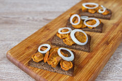 Sandwiches with mushrooms and onions. On a wooden board Royalty Free Stock Photography