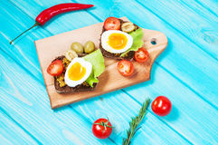 Sandwiches with olive, quail eggs, cherry tomatoes and potatoes. On a wooden blueboard. Delicious healthy snack or Breakfast Stock Images