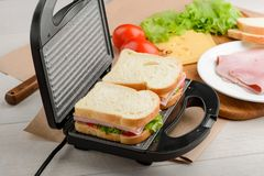 Sandwiches in a panini press. Making of yummy snacks with ham, cheese and vegetables royalty free stock photography
