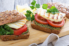 Sandwiches with pesto, vegetables and haloumi. Sandwiches with pesto, tomatoes and grilled haloumi Stock Photos