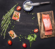 Sandwiches with pink salmon fillet, curd cheese, herbs and cherry tomatoes lined frame a black wooden background backdrop place Royalty Free Stock Photography