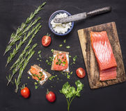 Sandwiches with pink salmon fillet, curd cheese, herbs and cherry tomatoes on wooden rustic background top view close up Stock Images