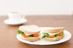 Sandwiches on a plate and cup of coffee on a wooden background Royalty Free Stock Photos