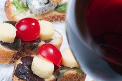 Sandwiches on plate and glass of red wine. Sandwiches on clear plate and glass of red wine out of focus Royalty Free Stock Photos