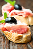 Sandwiches with prosciutto olive on wooden cutting board vertica Stock Images