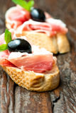 Sandwiches with prosciutto olive on wooden old table vertical Stock Photos