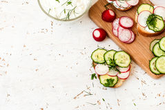 Sandwiches with radish and sour cream sauce. Spring snacks sandwiches with radish, cucumber and cream sauce. cream cheese with a plate and parsley Royalty Free Stock Photography
