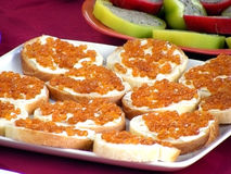 Sandwiches with red caviar. White dish with sandwiches with red caviar is on the red tablecloth Royalty Free Stock Image