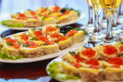 Sandwiches with red caviar and champagne on the table. Sandwiches with red caviar, lemon,olives and champagne on the table Stock Photo