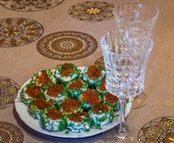 Sandwiches with red caviar and greens on a plate and two glasses royalty free stock images