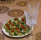 Sandwiches with red caviar and greens on a plate and two glasses royalty free stock photos