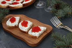 Sandwiches with red caviar are located on a wooden board royalty free stock images