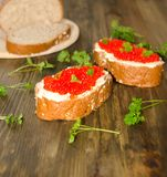 Sandwiches with red caviar and a number of greens on a wooden background selective stock photos