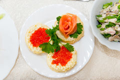 Sandwiches with red caviar and salmon are spread on a plate on a buffet table close up. Stock Photos