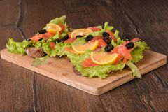 Sandwiches with red fish. On a cutting board stock images