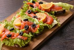 Sandwiches with red fish and lemon. On a cutting board Royalty Free Stock Photo