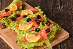 Sandwiches with red fish and lettuce. On a cutting board royalty free stock photos