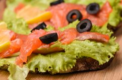 Sandwiches with red fish, lettuce, lemon and olives. Close up stock photography
