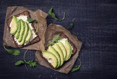 Sandwiches with rye bread and fresh sliced avocado. Sandwiches with rye bread, fresh sliced avocado and arugula royalty free stock photos