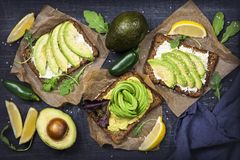 Sandwiches with rye bread and fresh sliced avocado. Sandwiches with rye bread, fresh sliced avocado and arugula stock photo