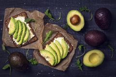 Sandwiches with rye bread and fresh sliced avocado. Sandwiches with rye bread, fresh sliced avocado and arugula royalty free stock images