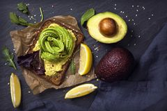 Sandwiches with rye bread and fresh sliced avocado. Sandwiches with rye bread, guacamole and fresh avocados royalty free stock photos