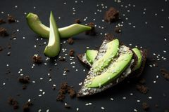 Sandwiches with rye bread, fresh sliced avocado and scattered crumbs on a black background stock images