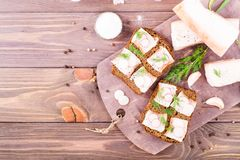 Sandwiches from rye bread, salted bacon, radish and dill. On a cutting board on a wooden table. Top view Stock Image