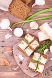 Sandwiches from rye bread, salted bacon, radish and dill. On a cutting board on a wooden table. Top view Royalty Free Stock Image