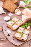 Sandwiches from rye bread, salted bacon, radish and dill. On a cutting board on a wooden table Royalty Free Stock Photo