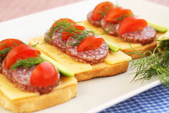 Sandwiches. With salami, cheese, cherry tomato and dill on plate Stock Photos
