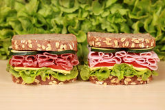 Sandwiches with salami and ham. Fresh sandwiches with salami and ham served with cheese and lettuce on a wooden table stock photography