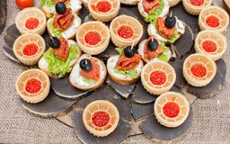 Sandwiches with salami and olives, baskets of red caviar. On a wooden plate royalty free stock photos