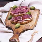 Sandwiches with salami sausage and hamon. On a brown wooden board, close up Stock Photos