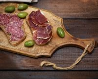 Sandwiches with salami sausage and hamon. On a brown wooden board Stock Photos