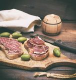 Sandwiches with salami sausage and hamon. On a brown wooden board, vintage toning Royalty Free Stock Image
