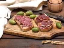 Sandwiches with salami sausage and hamon. On a brown wooden board, close up Royalty Free Stock Photos