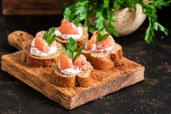 Sandwiches with salmon. Canape with red fish, rye bread, soft cheese, parsley and spices. Selective focus. Sandwiches with salmon. Canape with red fish, rye royalty free stock images