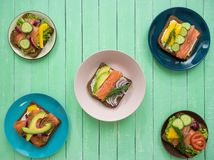 Sandwiches with salmon, black bread and vegetables in plates on the table. Sandwiches with salmon, cream cheese, black bread and vegetables in plates on an old stock photo