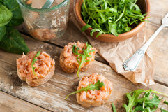 Sandwiches with salmon pate and arugula. Several sandwiches with salmon pate and arugula, fish bruschetta. Rustic homemade Italian cuisine royalty free stock photos