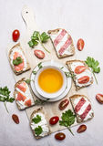 Sandwiches with salmon and salami, parsley tea and lunch on wooden rustic background top view Royalty Free Stock Image
