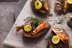 Sandwiches with sardines and quail eggs on a parchment Royalty Free Stock Photography