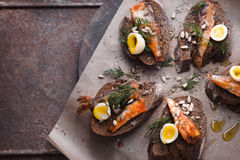 Sandwiches with sardines and quail eggs on right Stock Photo