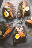 Sandwiches with sardines and quail eggs on the table Stock Images