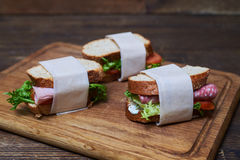 Sandwiches with sausage, tomatoes and salad and bread wrapped in Royalty Free Stock Images