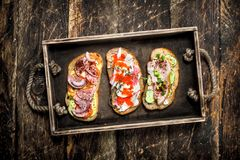 Sandwiches with seafood, salami, bacon and fresh vegetables. Royalty Free Stock Photo