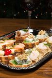Sandwiches on silver tray. Tray with sandwiches on holiday table with wine and Christmas tree with lights on background stock photo