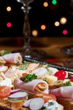 Sandwiches on silver tray. Tray with sandwiches on holiday table with wine and Christmas tree with lights on background Stock Images