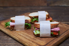 Sandwiches with slices of sausage, tomatoes and lettuce wrapped Stock Photo